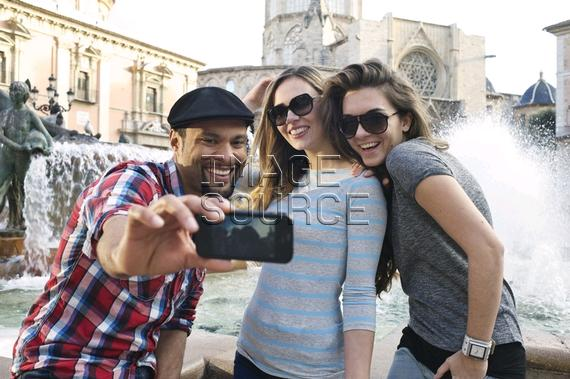 Tourist friends taking self portrait, Plaza de la Virgen, Valencia, Spain